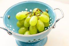 Świezi zieleni winogrona w błękitnym metalu colander Obrazy Royalty Free