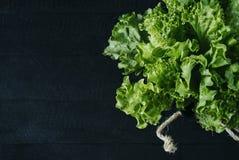 Świezi zielonej sałatki sałaty liście odizolowywający na ciemnym tle starzejący się drewnianych desek rocznika horyzontalny odgór zdjęcia stock