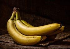 Żółci banany na drewno stole Zdjęcia Royalty Free