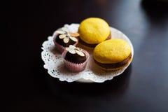 Żółci macaroons i czekoladowi cukierki kłamają na białym talerzu obrazy stock