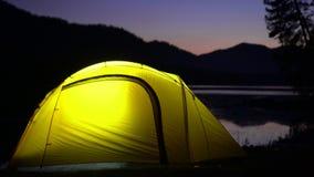 Żółci namiotów koszty na banku halny jezioro noc W światła namiotowych oparzenie zdjęcie wideo