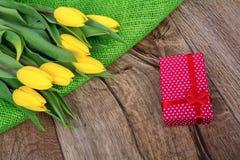 Żółci tulipany i prezent na drewnianym stole Obraz Royalty Free