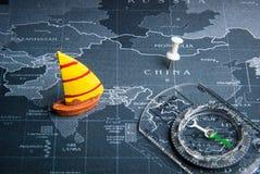 Żółta żaglówka i kompas na światowej mapy szpilce Porcelanowy countr Zdjęcie Stock