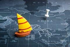 Żółta żaglówka na światowej mapy szpilce Porcelanowi kraje Biznes Obrazy Royalty Free