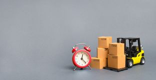 Żółta Forklift ciężarówka z kartonami i czerwonym budzikiem Ekspresowej dostawy poj?cie Chwilowy magazyn, ograniczająca oferta fotografia royalty free