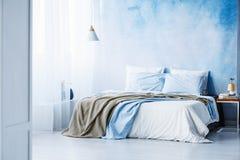 Żółta i błękitna pościel na białym łóżku w minimalnym sypialni wnętrzu zdjęcia stock