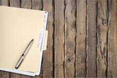 Żółta kartoteki falcówka, pióro na drewnianym tle i Fotografia Royalty Free