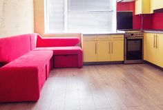 Żółta kuchnia z spiżarniami, okno, laminatem i czerwieni miękkiej części cou, obrazy stock