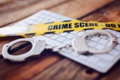 Żółta miejsce przestępstwa taśma, kajdanki na komputerowej klawiaturze i Zdjęcie Stock