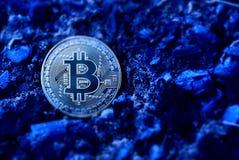 Żółta moneta kłama na czarnej błękit ziemi Obrazy Stock