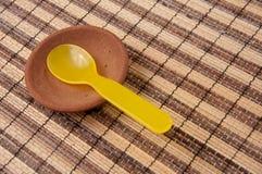 Żółta plastikowa łyżka w glinianym dysku Fotografia Stock