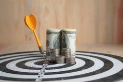 Żółta strzałki strzała uderza centrum cel dartboard c i pieniądze fotografia stock