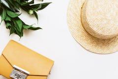 Żółta torba, roślina i słomiany kapelusz na beżowym tle, zdjęcie royalty free