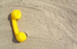 Żółta tubka stary rocznika telefon jest płaskim lying on the beach na piasku z odbitkową przestrzenią dla twój teksta z kontaktam fotografia stock