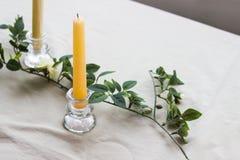 Żółta wosk świeczka na stole w candlestick Zdjęcie Stock