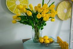 Żółte cytryny i żółci tulipany na stole zdjęcie stock