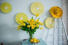 Żółte cytryny i żółci tulipany na stole zdjęcia stock