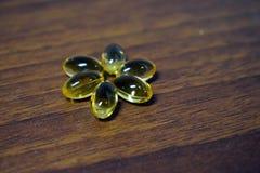 Żółte przejrzyste kapsuły na drewnianym tle, zdrowy pojęcie obraz stock