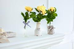 Żółte róże w białym dzbanku na bielu stole przeciw neutralnemu tłu zdjęcia royalty free