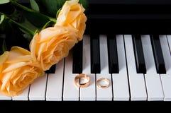 Żółte róże z obrączkami ślubnymi na pianinie narz?dzanie ?lub Prezent twój ukochany dla ślubu lub walentynka dnia obrazy stock