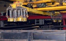 Żółtego metalu część zawieszająca na łańcuchu maszyna dla przetwarzać żelazne budowy w warsztacie samochód roślina obrazy royalty free