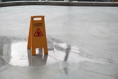 Żółtego ostrożności mokrego podłogowego cleaning w toku znak na mokrej podłoga zdjęcia royalty free