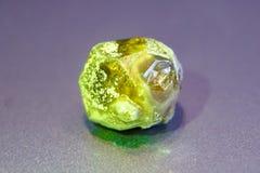 Żółtej zieleni nephritis na szarym tle, makro- fotografia royalty free