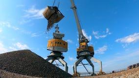 Żółty żuraw pracuje przy dokami, rozładunkowi udziały gruz zbiory