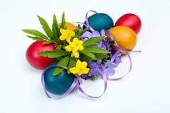 Żółty anemon i barwinek kwitniemy bukiet i sześć malujących Easter jajek na bielu fotografia stock