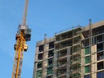 żółty budowa żuraw obok wielkiego betonowego budynku w budowie z rusztowaniem i dźwignikiem góruje obraz stock