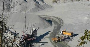 Żółty buldożer ładuje granit w żółtego usyp ciężarówki ciało, pracuje proces w łupie, kamienny łup, pracuje w a zdjęcie wideo