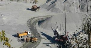 Żółty buldożer ładuje granit w żółtego usyp ciężarówki ciało, pracuje proces w łupie, kamienny łup, pracuje w a zbiory wideo
