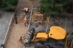 Żółty ciągnik Pracownik budowlany instaluje chodniczka bruk Kamienna ścieżka Odgórny widok Rishon Le Zion 2018 Obraz Stock