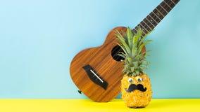 Żółty dojrzały ananas z czarnej wąsy gitary żółtym błękitnym tłem ?miesznego kagana tropikalna owoc Partyjny poj?cie fotografia royalty free