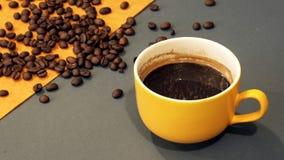 Żółty filiżanka kawy na szarym i żółtym tle z kawowymi fasolami obraz stock