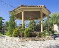 Żółty gazebo, arbour z kwiatami i drzewo przy kościół, uprawiamy ogródek podwórze przy sidari, Corfu Greece zdjęcia stock