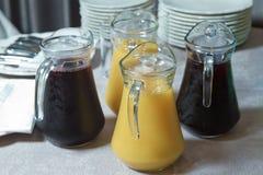 Żółty i czerwony Szklany miotacz żółty i czerwony smoothie sok Wyśmienicie sok pomarańczowy w dzbanku uice w ciężkiej szklanej dz fotografia stock