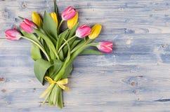Żółty i czerwony tulipanu bukiet z faborkiem na błękitnej podławej modnej drewno desce Kwiecień wiosny Easter tło obrazy royalty free