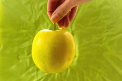 Żółty jabłko w ręce na zielonym tle fotografia royalty free