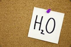 Żółty kleisty nutowy writing, podpis, wpisowy zwrot H2O w czarnym ext na kleistej notatce przyczepiającej korkowa zawiadomienie d Fotografia Royalty Free