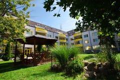Żółty kompleks mieszkaniowy dom park w podwórko - blok mieszkalny - obrazy stock
