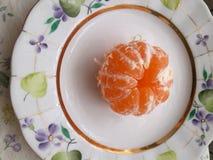 Żółty mandaryn na koloru talerzu fotografia stock
