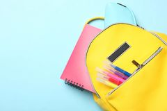 Żółty plecak z różnymi szkolnymi dostawami fotografia stock