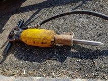 Żółty pneumatyczny dźwigarka młot na asfalcie fotografia stock