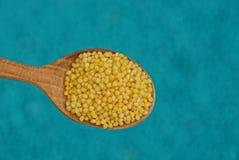 Żółty round zboże w drewnianej łyżce na błękitnym tle Fotografia Stock