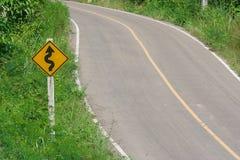 Żółty ruchu drogowego znaka ` labiryntu ruchu drogowego ` na zielonym krzaku obok drogi Fotografia Royalty Free