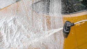 Żółty samochód mył przy carwash - biały gęsty piany i szamponu splu zdjęcie royalty free