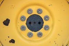 Żółty tło W górę fotografii żółty ciągnikowy koło z dokrętkami rygle - i - Makro- zdjęcie royalty free