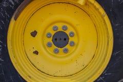 Żółty tło W górę fotografii żółty ciągnikowy koło z dokrętkami rygle - i - Makro- obraz royalty free