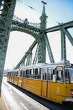 Żółty tramwaj krzyżuje swoboda most Budapest Hungagry, Wrzesień -, 12, 2018 - fotografia royalty free